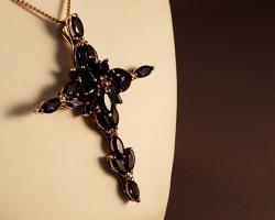 A 9ct gold cross filled of Vivid dark Tanzanites